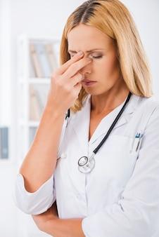 Het was een lange dag in het ziekenhuis. depressieve vrouwelijke arts in wit uniform die haar neus aanraakt