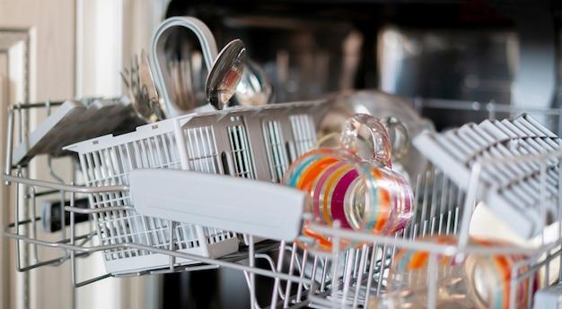 Het wat vuile vaatwerk op het dienblad in de vaatwasser in de keuken?