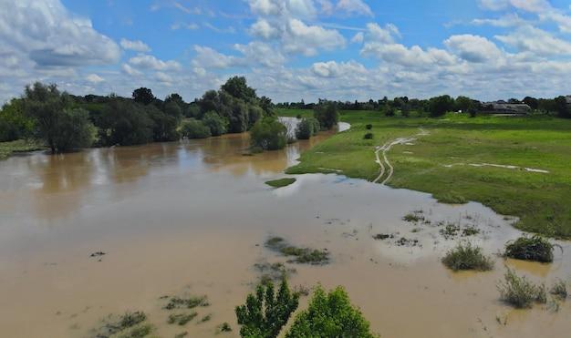 Het water dat in de waterweg van het landbouwbedrijfgebied stroomt op gebied overstroomde schade na zware regen