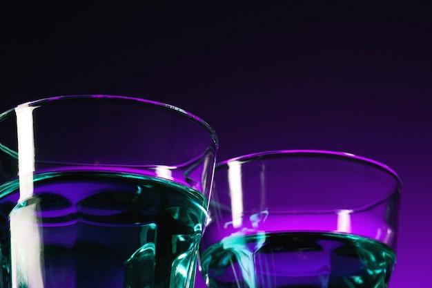 Het water in twee glazen op lila achtergrond in de studio. levendige heldere gekleurde verlichting. trendy in 2018 ultra violet gloeilamp. kunstdecoratie met een mystieke kleur