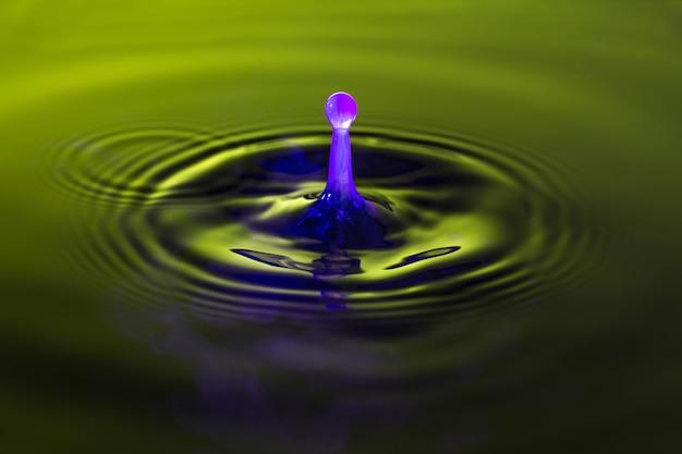Het water met melk druppelt kleur dichte macro