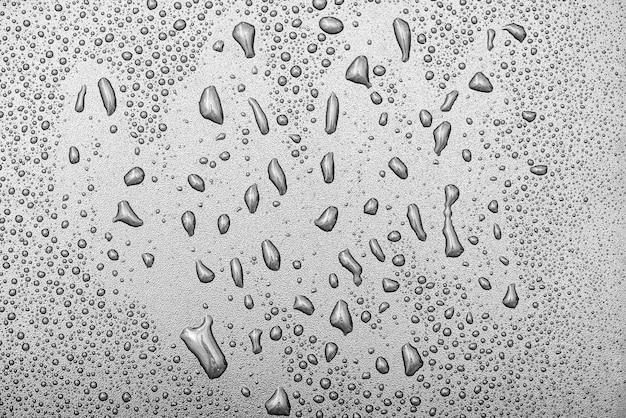 Het waterdalingen van de close-up op oppervlakte van grijze achtergrond, watertextuur, hoogste mening