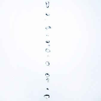 Het waterdalingen van de close-up op witte achtergrond