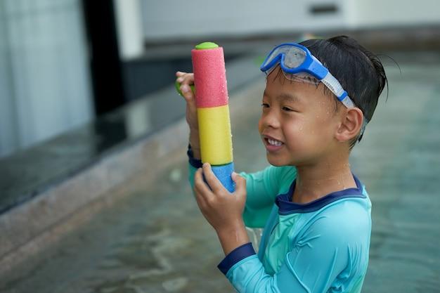Het waterkanon van het jongensspel met beschermende brillen in het concept van de hotelvakantie