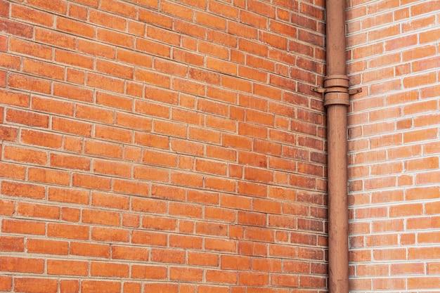 Het waterleidingsysteem installeert bij de oranje bakstenen muur