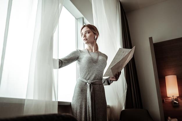 Het weer bekijken. zakenvrouw die stijlvolle grijze jurk draagt die venster onderzoekt en weer controleert