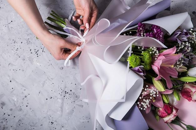 Het werk van de bloemist in het proces van het creëren van een boeket met lelies op de werkplek