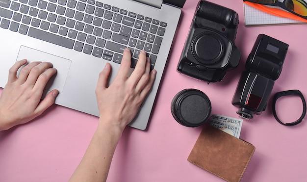 Het werk van de fotograaf, retoucheren van foto's. het fotografische materiaal, vrouwelijke handen die op laptop toetsenbord op roze pastelkleurachtergrond typen, hoogste mening, vlak concept freelancing, lag