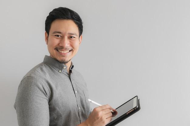 Het werk van de gelukkige en glimlachondernemerszakenman op zijn tablet met grijze achtergrond.