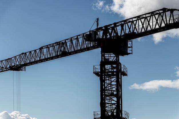 Het werk van een torenkraan tegen de blauwe lucht in de achtergrondverlichting. moderne woningbouw. silhouet van een torenkraan close-up.