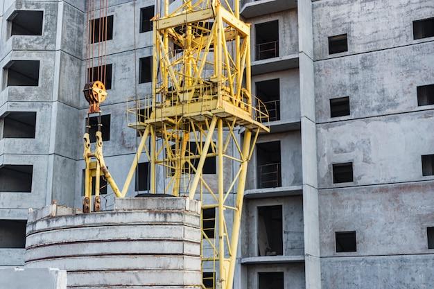 Het werk van een torenkraan tijdens de bouw van een paneelhuis van gewapend beton