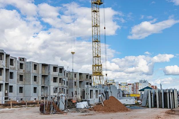 Het werk van torenkranen tegen de achtergrond van de avondrood. moderne woningbouw. industriële techniek. bouwen van hypotheken.