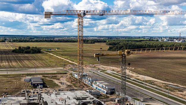 Het werk van torenkranen tegen de achtergrond van de bewolkte hemel aan de rand van de stad. moderne bouwconstructie. grote bouwplaats.