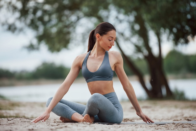 Het werk van vandaag is goed gedaan. brunette met mooie lichaamsvorm in sportieve kleding heeft fitnessdag op een strand