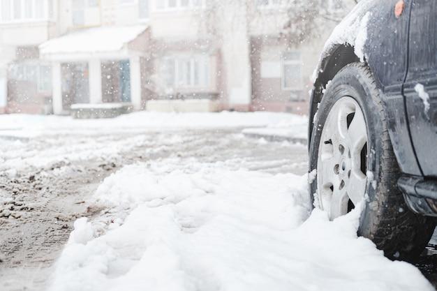 Het wiel van een auto onder natte sneeuw.
