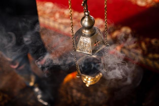 Het wierookvat van de priester hangt aan een oude muur in de orthodoxe kerk. koperen wierook met brandende kolen erin. service in het concept van de orthodoxe kerk. aanbidding