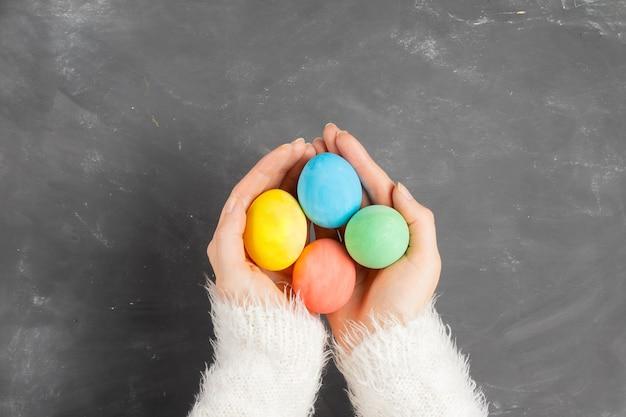 Het wijfje dient een witte pluizige sweater in houdt kleurrijke paaseieren over een schoolbord