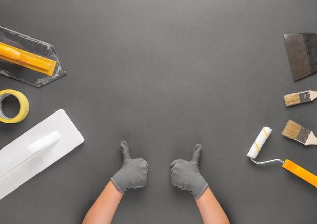 Het wijfje dient handschoenen in die duimen op grijze achtergrond met hulpmiddelen voor huisrenovatie tonen.