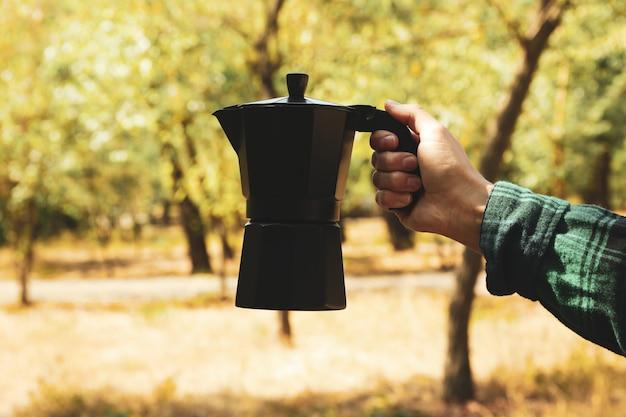 Het wijfje dient het koffiezetapparaat van de overhemdsgreep openlucht in