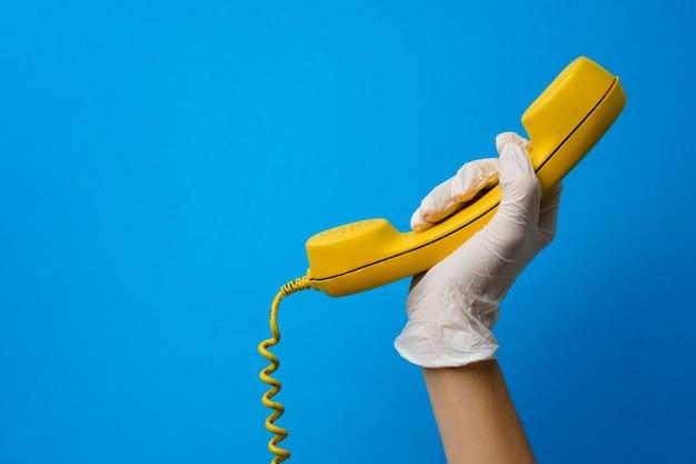 Het wijfje dient medische handschoen in die gele telefoonspreker houdt