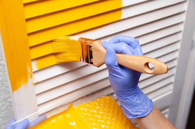 Het wijfje dient rubberhandschoen met borstel in schilderend houten deur met gele verf