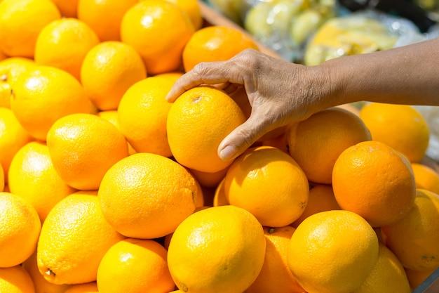 Het wijfje dient sinaasappel in supermarkt met de hand op