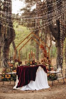Het wijnpresidium van de pasgetrouwden in de feestzaal van het restaurant is versierd met kaarsen en groene planten, blauweregen hangt aan het plafond