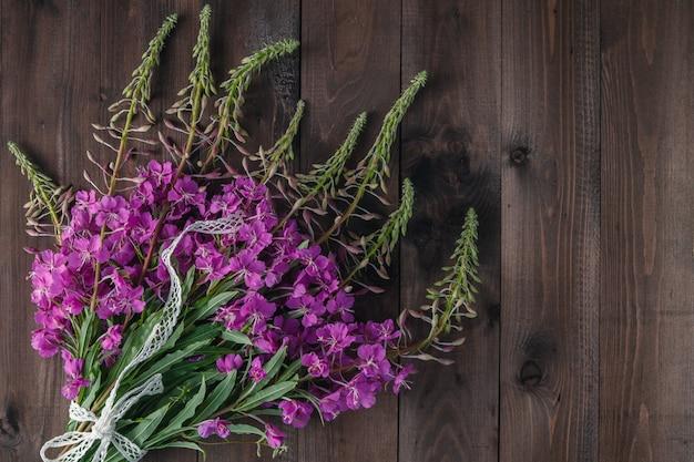 Het wilgeroosje bloeit vers op een houten raadsachtergrond