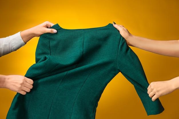 Het winkelconcept. de vrouwelijke handen met jurken op geel.