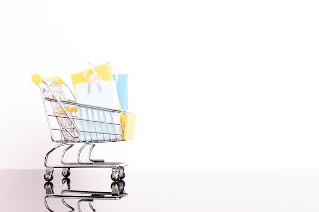 Het winkelen autohoogtepunt van zakken op witte muur