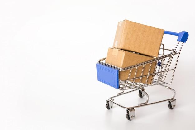 Het winkelen concept: kartons of document vakjes in blauw boodschappenwagentje op wit met exemplaarruimte