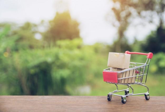 Het winkelen concept: kartons of document vakjes in boodschappenwagentje op bruine houten lijst.