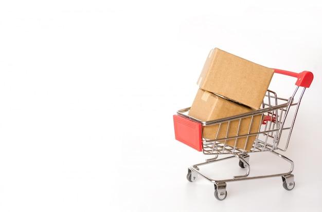 Het winkelen concept: kartons of document vakjes in rood boodschappenwagentje op witte achtergrond. online