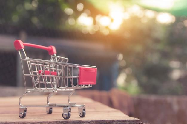 Het winkelen concept - leeg rood boodschappenwagentje op bruine houten lijst. online winkelende consumenten kunnen winkelen vanuit huis en bezorgservice. met copyspace