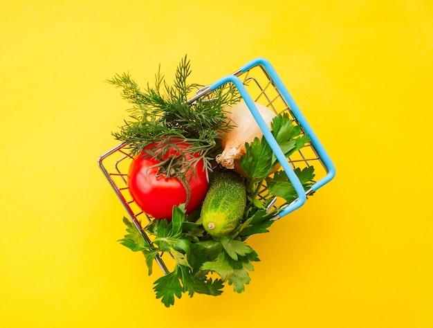 Het winkelen het metaal van de kruidenierswinkelkar op geel. voedsel mand concept. detailopname. plat leggen. selectieve zachte focus. . tekst kopie ruimte.