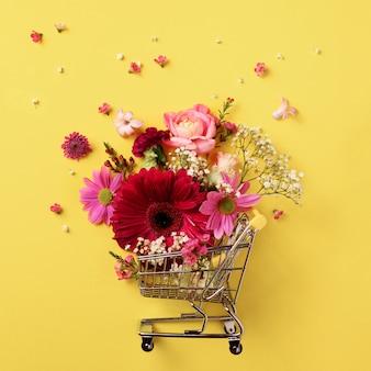 Het winkelen karretje met bloemen op gele punchy pastelkleurachtergrond.