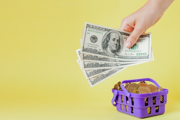 Het winkelen mand met muntstukken en dollarrekeningen in handen op gele .copyspace