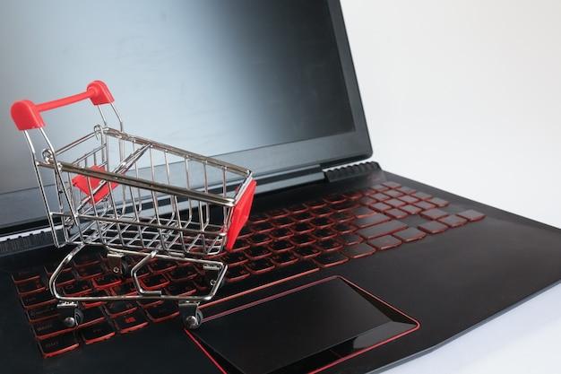 Het winkelen online concept - boodschappenwagentje op het zwarte toetsenbord. rode metalen trolley op een laptop toetsenbord