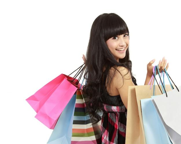 Het winkelen vrouw gelukkige het glimlachen holding het winkelen geïsoleerde zakken. heerlijk fris jong aziatisch vrouwelijk model.