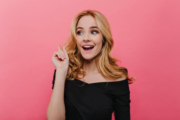 Het winnende blonde vrouw stellen met verbaasde glimlach. binnenfoto van wit geïnteresseerd meisje in zwarte jurk geïsoleerd op roze muur.