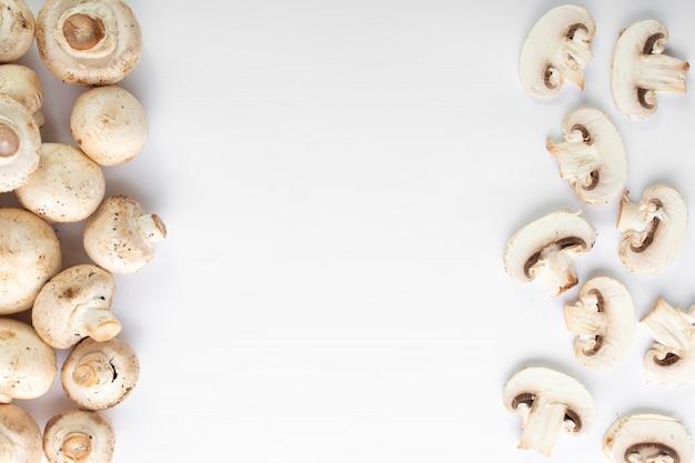 Het wit schiet verse champignons op witte vloer als paddestoelen uit de grond