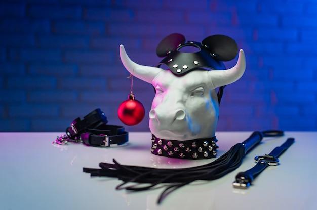 Het witmetalen stierbeeldje met een nieuwjaarsspeeltje in een leren masker en accessoires voor bdsm-spellen