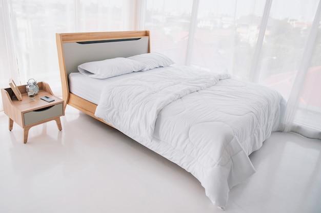 Het witte bed in de slaapkamer, er hangen witte gordijnen door de kamer.