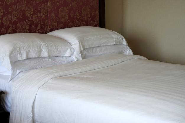 Het witte bed met twee kussens in de hotelkamer