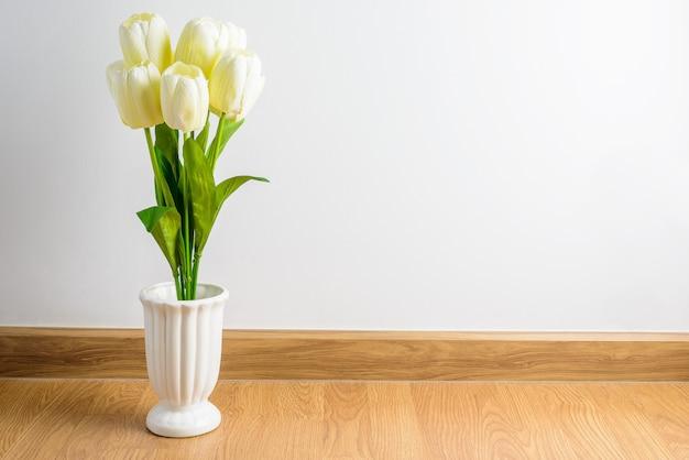 Het witte boeket van tulpenbloemen in vaas op houten vloer