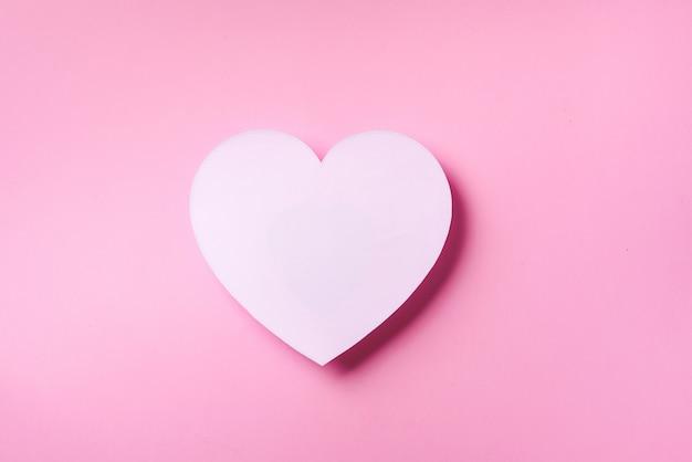 Het witte hart sneed van document over roze punchy pastelkleurachtergrond met exemplaarruimte.