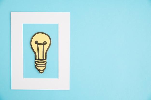 Het witte kader van de idee gloeilamp op blauwe achtergrond