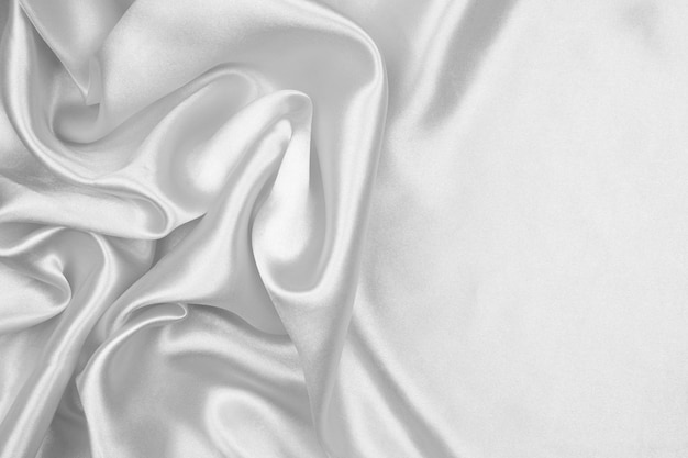 Het witte luxueuze satijn van de zijdetextuur voor abstracte achtergrond. mooie witte stof