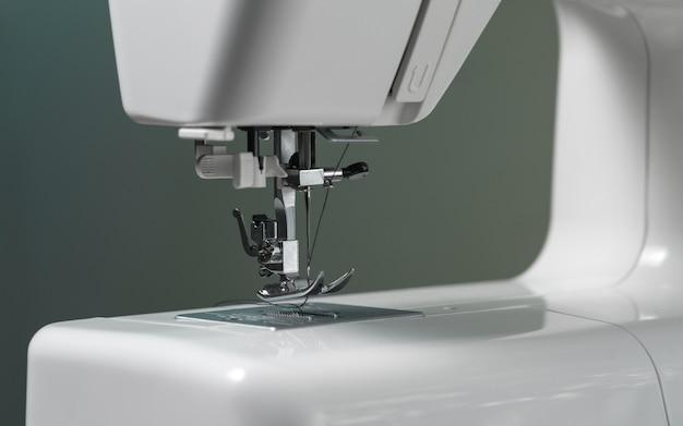 Het witte mechanisme van de naaimachinenaald dicht omhoog op groene grijze achtergrond