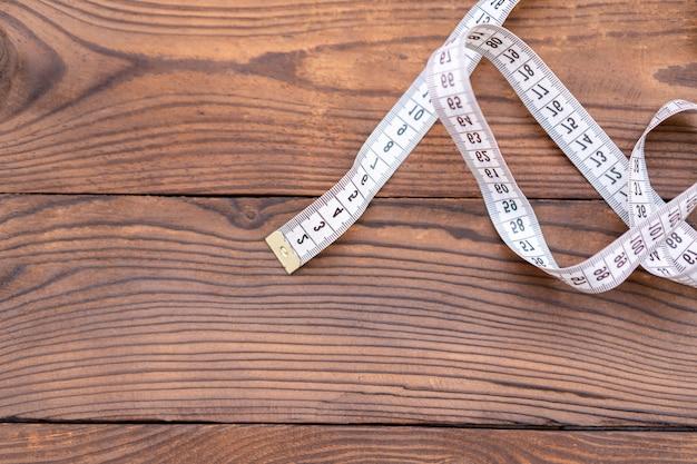 Het witte meetlint van een kleermaker ligt in hoek op donkere houten achtergrond. kopieer ruimte voor tekst